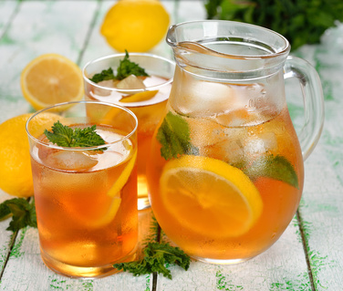 Ice tea with mint and lemon on a white table
